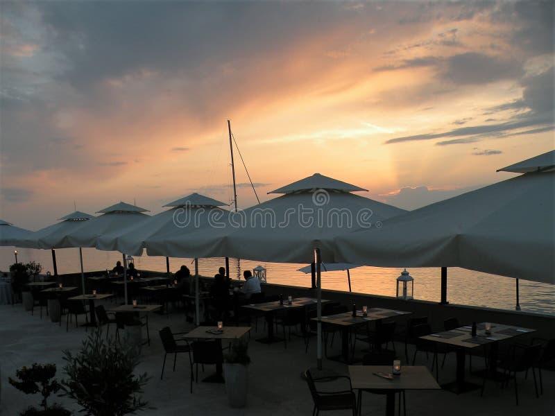 Folk på matställen, tabeller under vita paraplyer Restaurang vid havet Solnedgång Den medelhavs- platsen av ferie och turists tyc arkivfoton