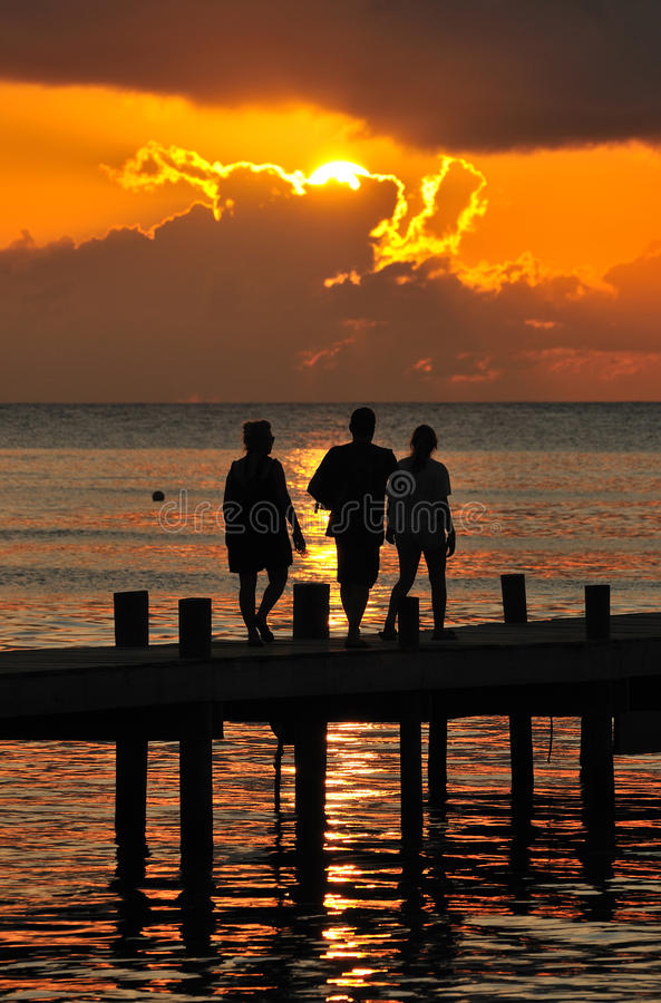 Folk på pir på solnedgången arkivbilder