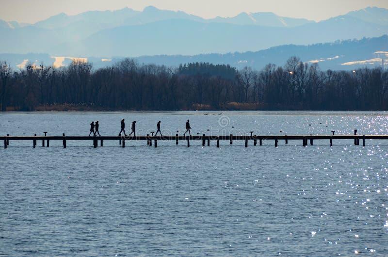 Folk på strandpromenaden på sjölandskapberg fotografering för bildbyråer