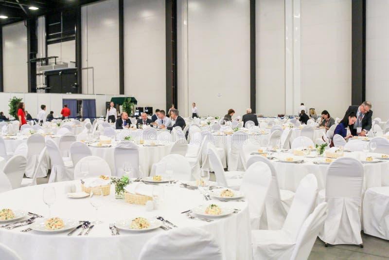 Folk på tabellerna i den stora korridoren royaltyfri fotografi
