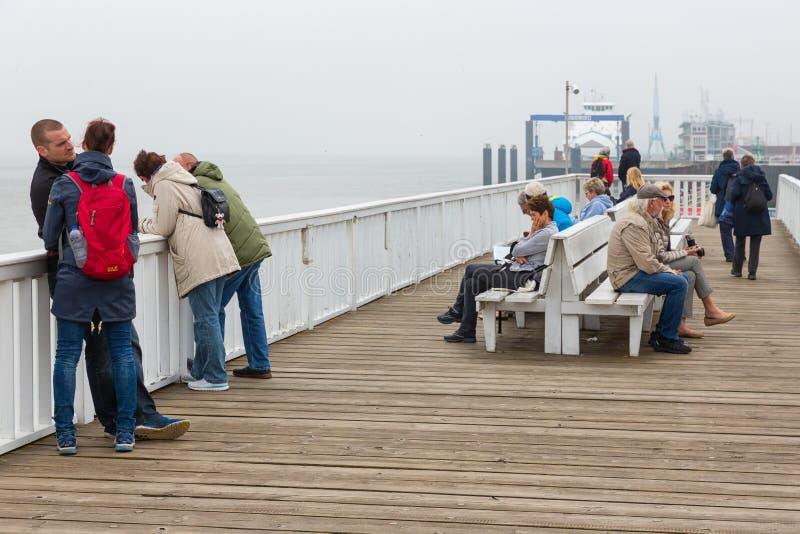 Folk på träpirCuxhaven den väntande på färjan till Helgoland royaltyfri bild