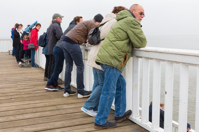 Folk på träpirCuxhaven den väntande på färjan till Helgoland royaltyfri foto