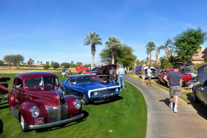 Folk på välgörenhetbilshowen som beundrar rader av den klassiska varma stången och specialintressebilar som parkeras på en golfba arkivbilder