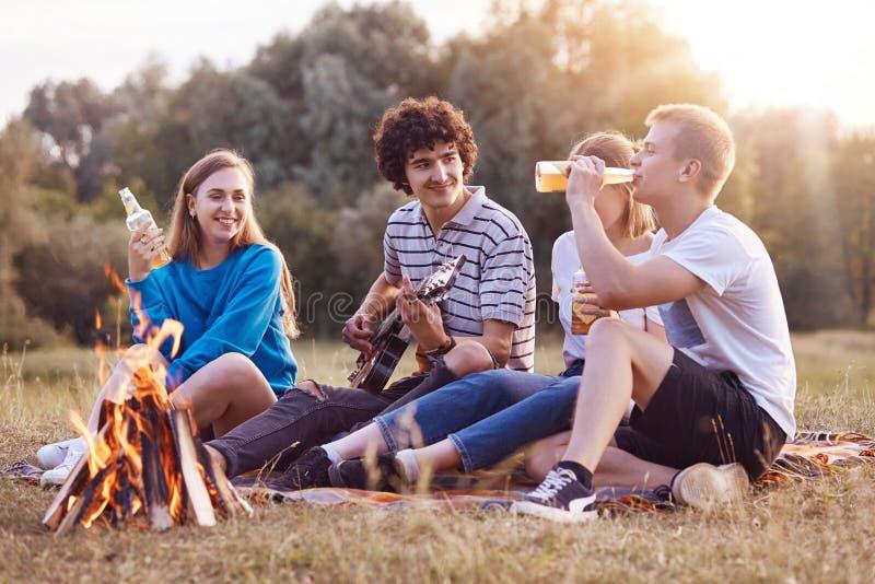 Folk-, picknick- och livsstilbegrepp Glade fyra vänner sjunger sång och spelar gitarren, sitter nära brasa, tycker om sommardrink royaltyfri bild
