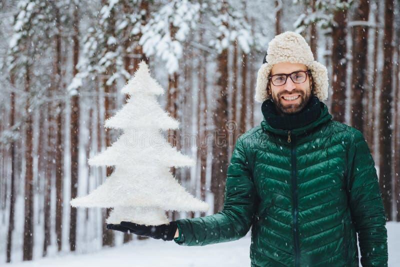 Folk, sinnesrörelser, snöig väder och säsongbegrepp Lycklig gladlynt ung orakad manlig iklädd varm kläder, rymmer granträdet, st royaltyfria bilder