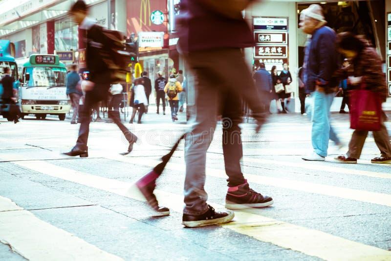 Folk som är rörande på sebraövergångsställe på den fullsatta staden Hong Kong fotografering för bildbyråer