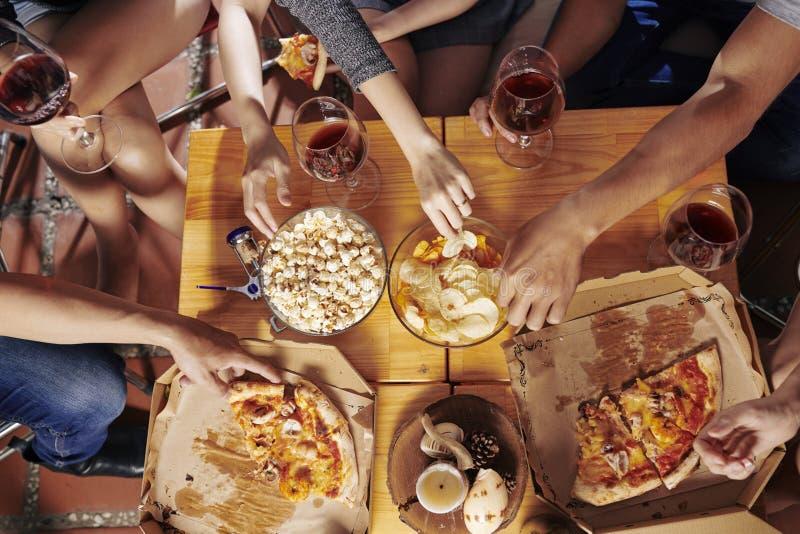 Folk som äter mellanmål på partiet arkivbilder