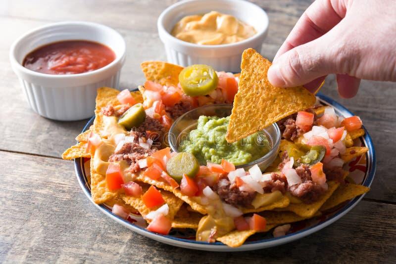Folk som äter mexikanska nachos med nötkött, guacamole, ostsås, peppar, tomaten och löken i platta på trä royaltyfri fotografi
