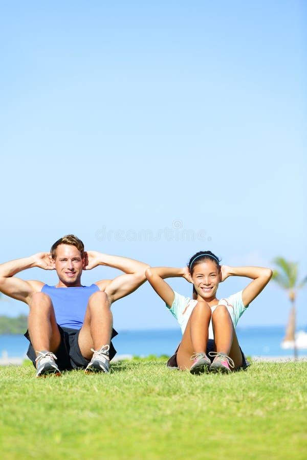Folk som övar - att göra för par sitter ups utomhus royaltyfri bild