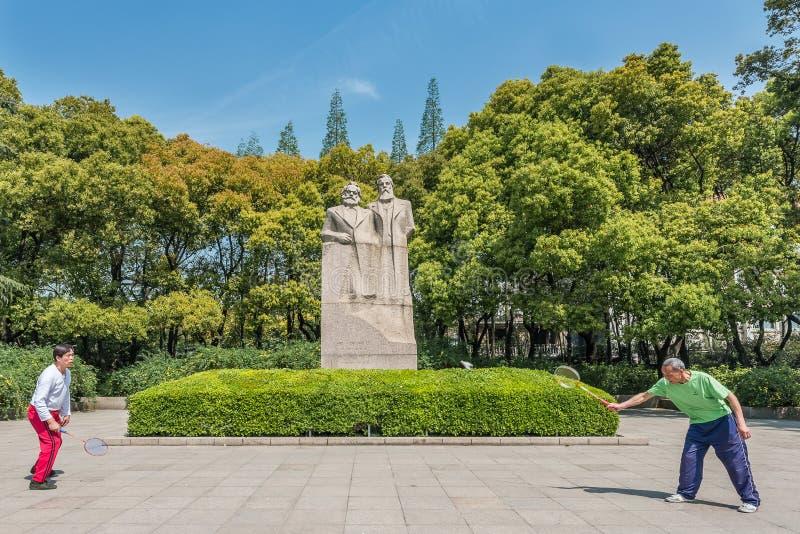 Folk som övar badminton marx och den engels statyn i den fuxing medeltalen royaltyfria foton