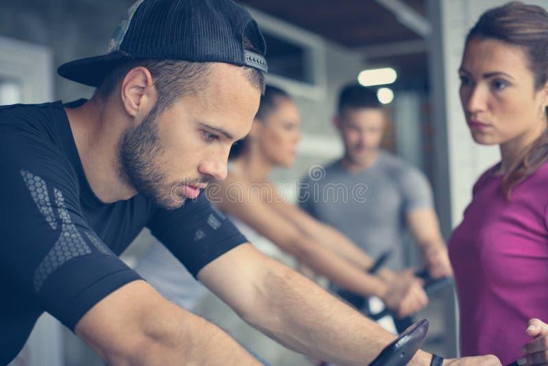 Folk som övar på stationära cyklar i konditiongrupp arkivfoto