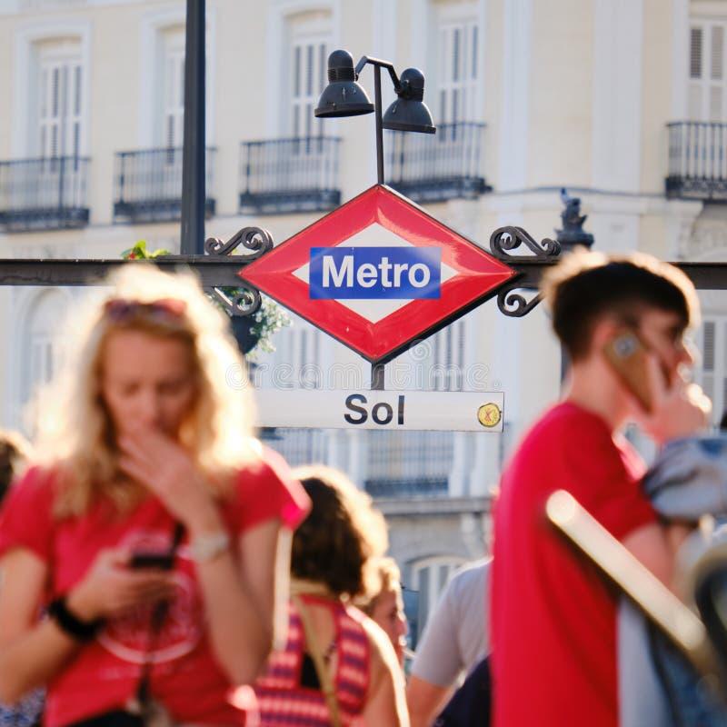 Folk som använder mobiltelefoner nära tunnelbanastation av solenoid i Madrid Spanien royaltyfri bild