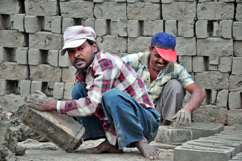 Folk som arbetar i tegelstenfabrik arkivfoto