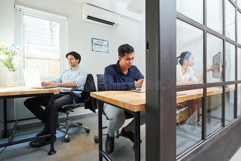 Folk som arbetar på det moderna kontoret arkivbilder