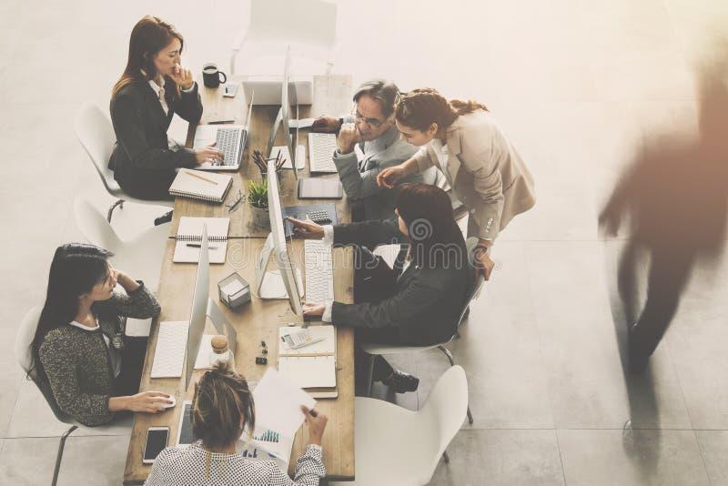 Folk som arbetar runt om en tabell arkivbild