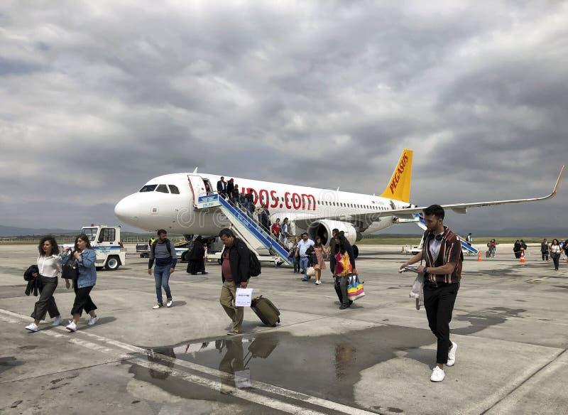 Folk som av får den Pegasus Airlines nivån på flygplatsen av Denizli i Turkiet arkivfoton