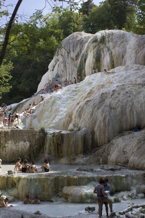 Folk som badar i Bagni San Filippo naturlig thermaltips arkivbild