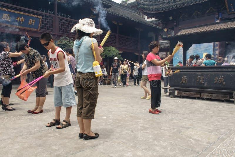 Folk som ber i stadsgudtemplet Chenghuang Miao på staden av Shanghai i Kina royaltyfria bilder