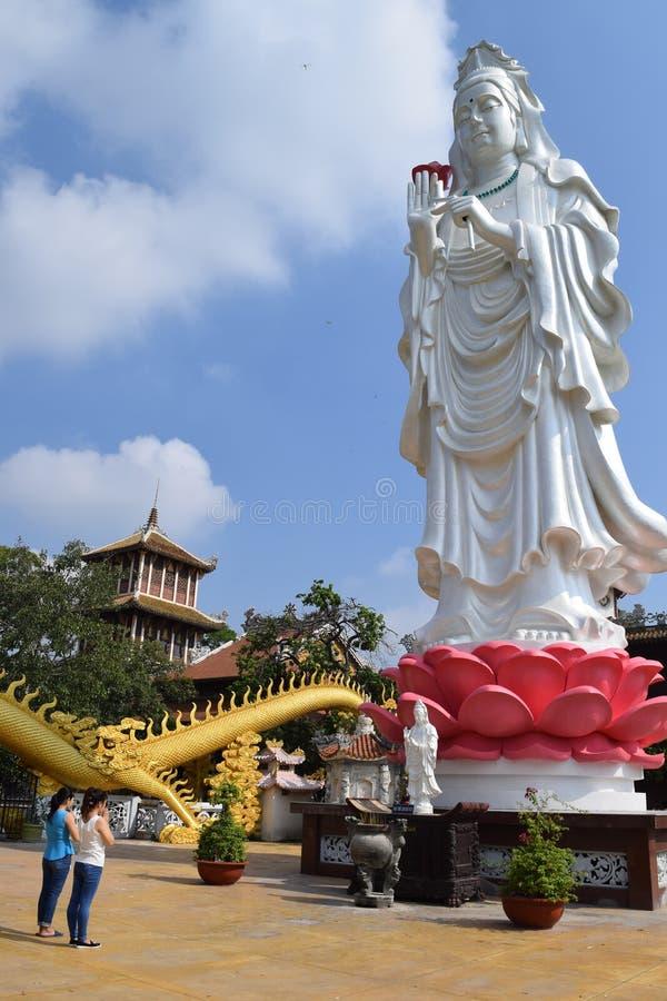 Folk som ber på den stora statyn av bodhisattvaen på buddisten Chau royaltyfria bilder