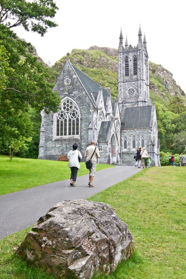 Folk som besöker dengotiska kyrkan på det Kylemore godset som är västra av Irland arkivbild