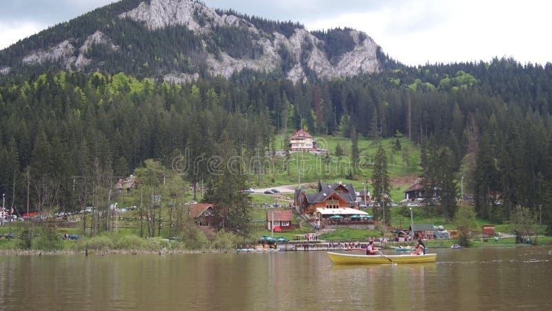 Folk som byggde deras hem på kanten av sjön och på foten av de gröna bergen arkivbilder