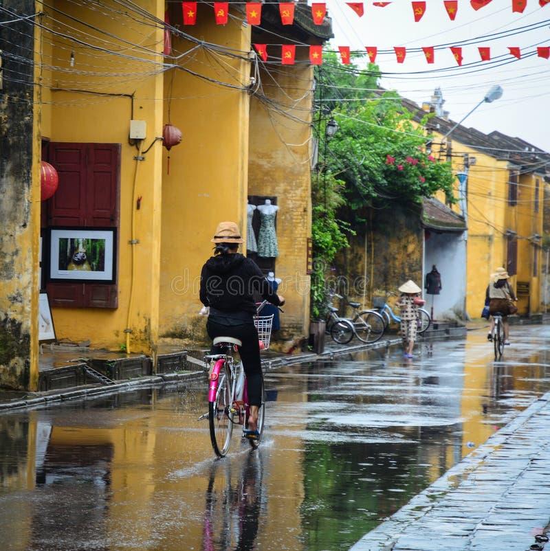 Folk som cyklar på gatan i Hoi An, Vietnam arkivbilder