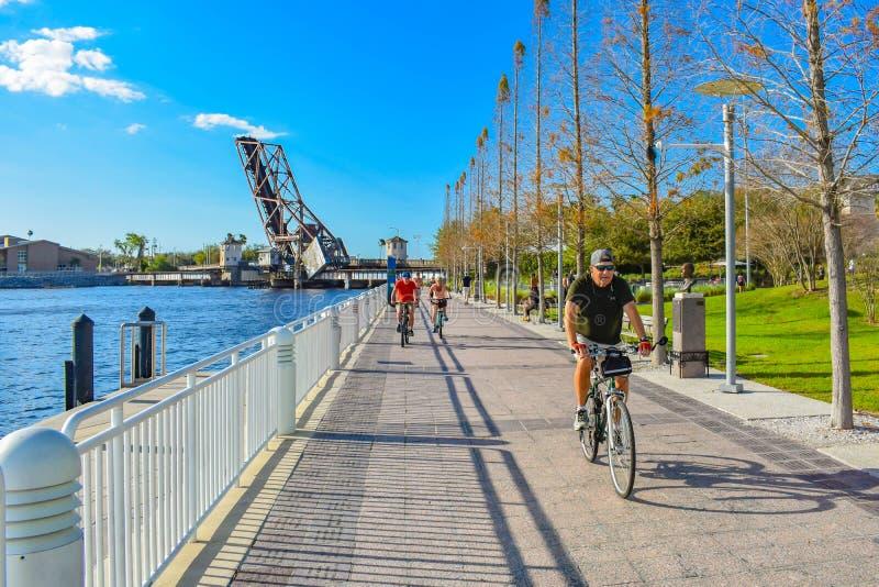 Folk som cyklar på Riverwalk i city fotografering för bildbyråer