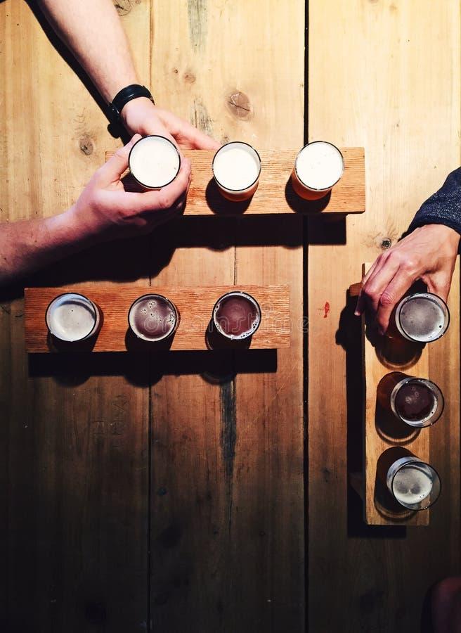 Folk som dricker lokalt öl från avsmakningpaletter på hantverkbryggeriet arkivbilder