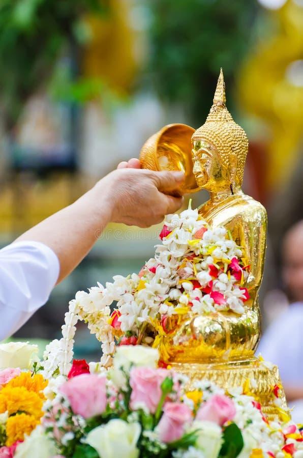 Folk som duschar den buddha statyn fotografering för bildbyråer