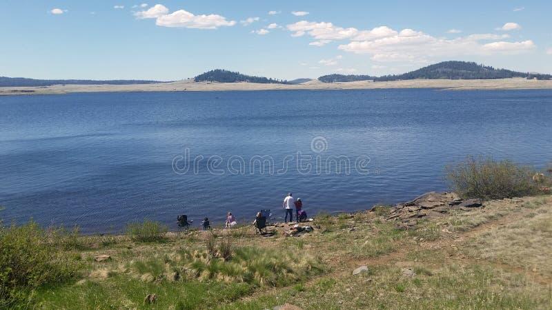 Folk som fiskar och tycker om dagen i en av de åtskilliga sjöarna av registreringen royaltyfria foton