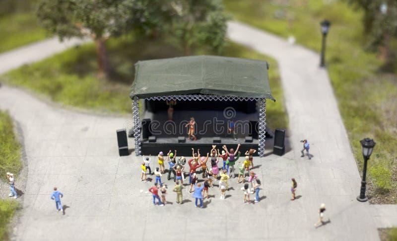 Folk som framme dansar i en parkera på en konsert av etappen i en miniatyrvärldsaktivering royaltyfri fotografi