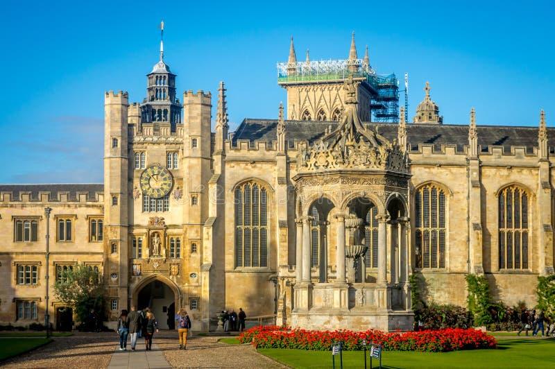 Folk som framme går av den berömda Treenighethögskolan på en ljus sommardag, Cambridge royaltyfria bilder