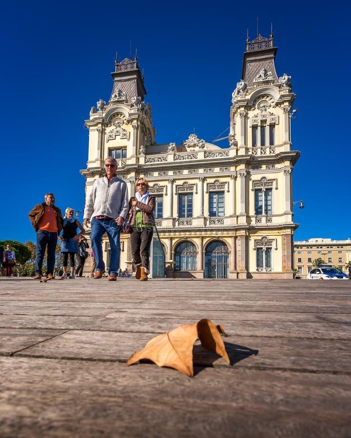 Folk som framme går på Rambla Del Mar av porten Vell arkivfoton