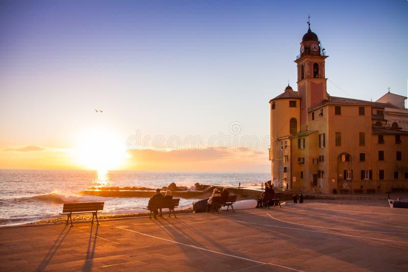 Folk som framme stirrar på solnedgången nära en kyrka av havet arkivfoton