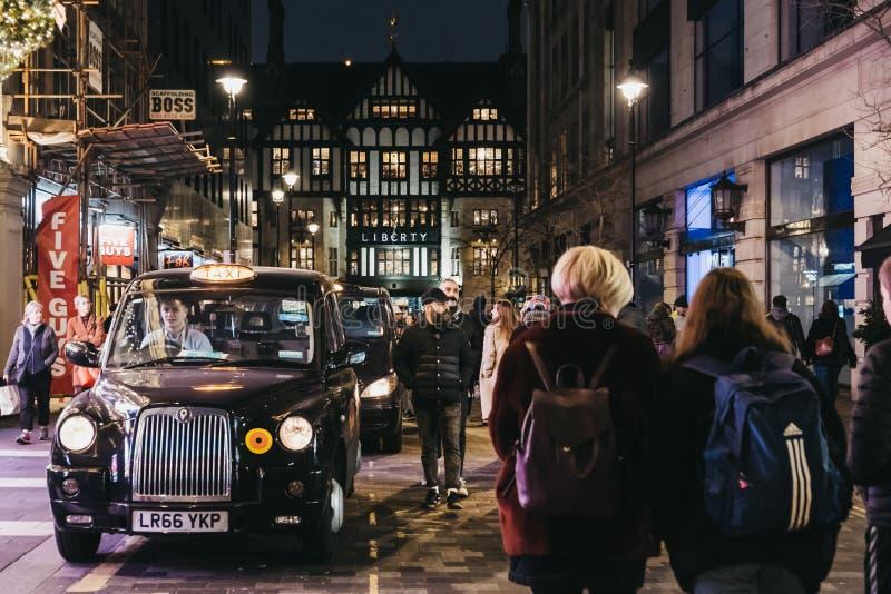 Folk som går förbi svarta taxiar som parkeras på den Argyll gatan, London, UK royaltyfri bild