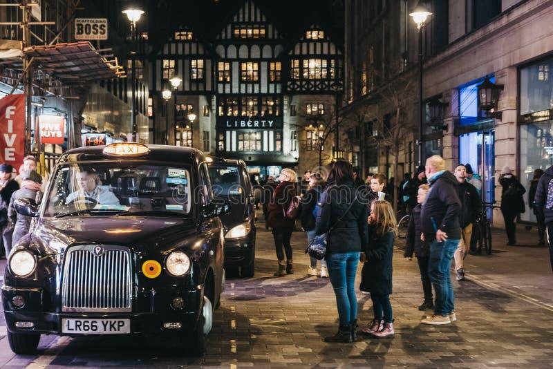 Folk som går förbi svarta taxiar som parkeras på den Argyll gatan, London, UK royaltyfria bilder