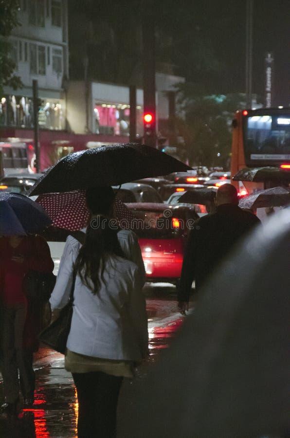 Folk som går i regnet arkivfoton