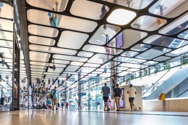 Folk som går inom den kommersiella korridoren av Amsterdam den centrala drevstationen royaltyfri foto