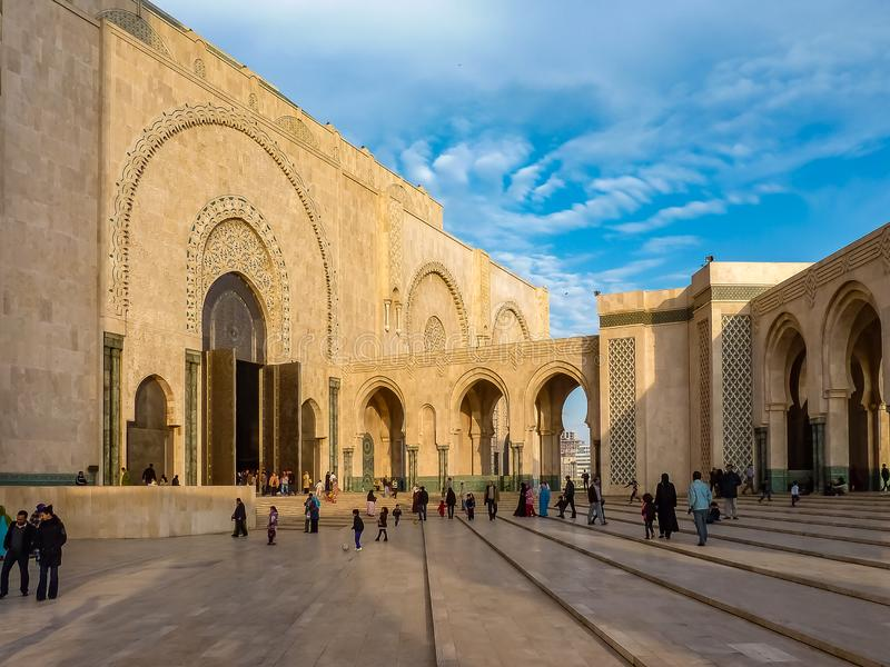 Folk som går nära de utsmyckade portarna av moskén Hassan II Casablanca, Marocko royaltyfri bild