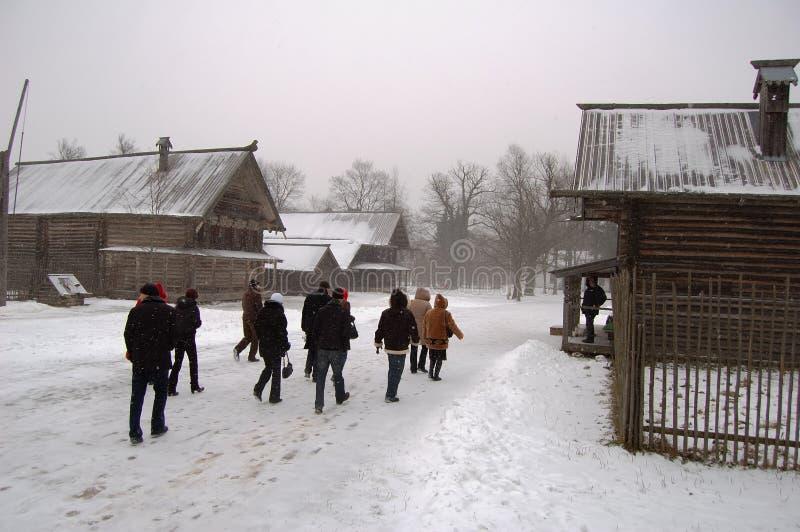 Folk som går nära trähus på vintern royaltyfria foton