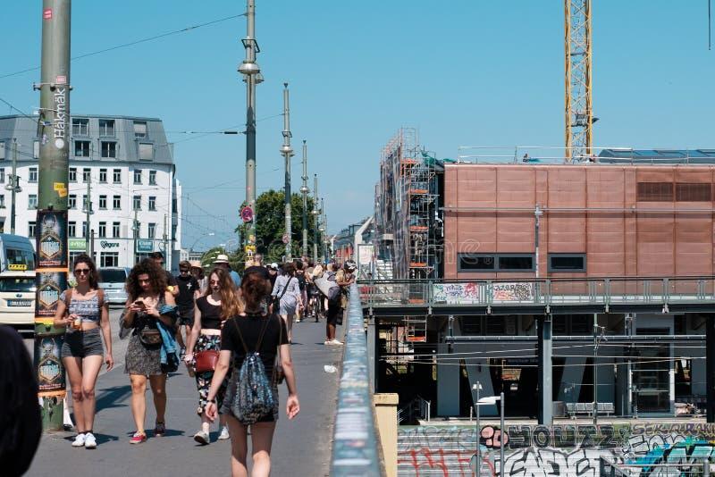 Folk som går på den fot- trottoaren på Warschauer Strasse i B arkivfoto