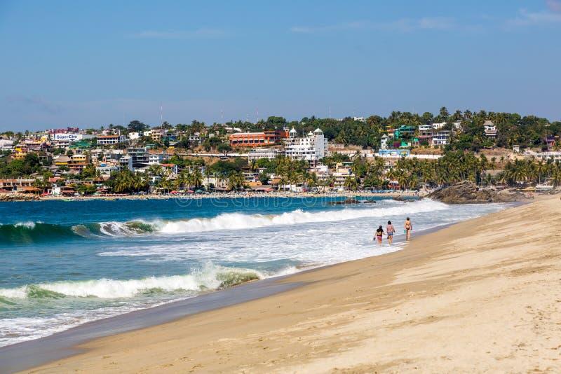 Folk som går på den Puerto Escondido stranden, royaltyfria foton