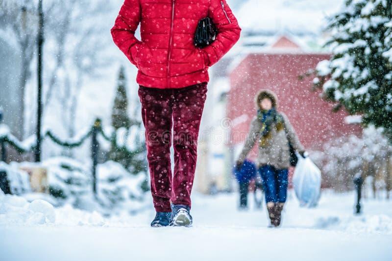 Folk som går på den snöig trottoaren fotografering för bildbyråer