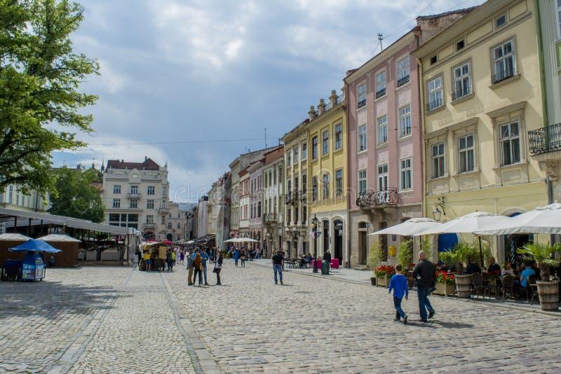 Folk som går på gatan i stad av Lviv i Ukraina arkivfoton