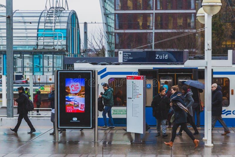 Folk som går på plattformen för att fånga drev i södra station av Amsterdam royaltyfri bild