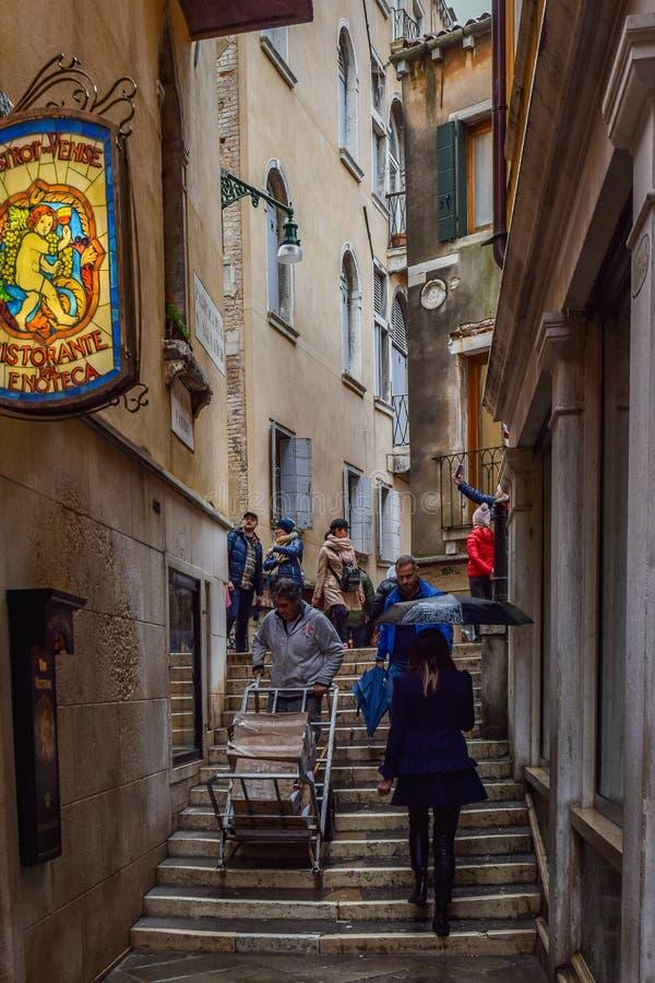 Folk som går på smal trappuppgång mellan byggnader i staden av Venedig, Italien arkivfoto