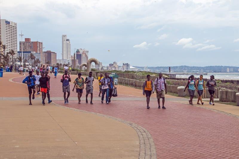 Folk som går på stenlagd promenad på Beachfront royaltyfria bilder