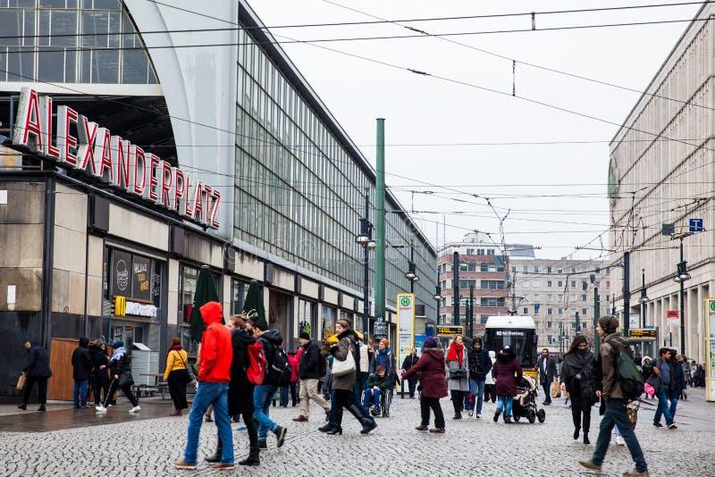 Folk som går runt om Alexanderplatz på det Berlin centret i ett kallt slut av vinterdagen royaltyfria foton