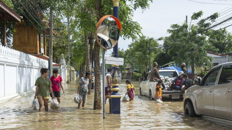 Folk som går till och med översvämmade gator arkivfoton