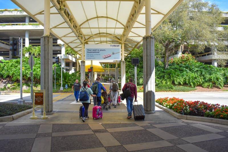 Folk som går till parkeringsplatsen med deras bagage på Orlando International Airport arkivfoto